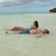 A Woman in a Swimsuit and a Man in Shorts Lie in the Sea By the Shore and Sunbathe - VideoHive Item for Sale