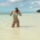 A Woman in a Swimsuit Is Kneeling in the Sea and Sunbathing - VideoHive Item for Sale
