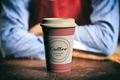 Coffee cup with a lid on a wooden bar with a blurry image of barista as background,