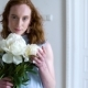 Portrait of Beautiful Red Haired Girl Sniffs a Big Bush of White Peonies - VideoHive Item for Sale