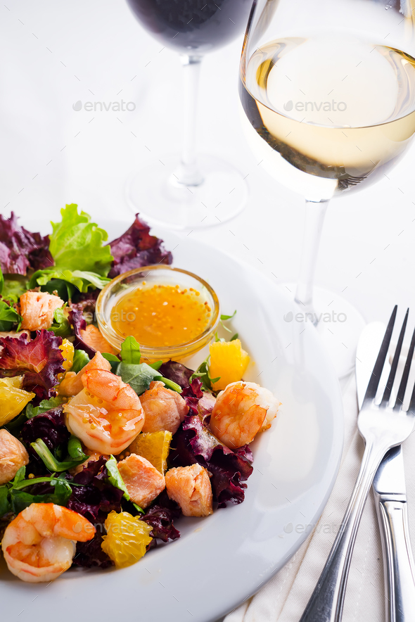 Healthy salad with prawns, lettuce, oranges and mango served on a plate with orange mustard sauce - Stock Photo - Images