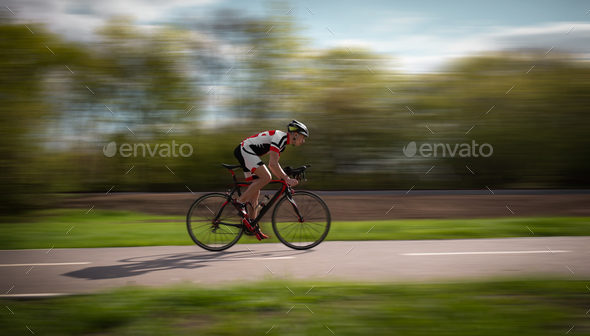 Cyclist rides on bicycle, speed effect, side view - Stock Photo - Images