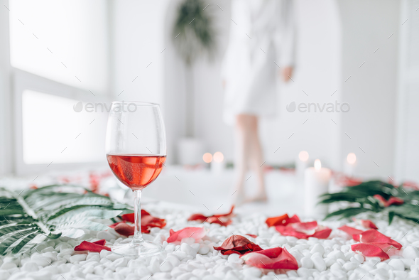 Woman dips legs into the bath, rose petal decor - Stock Photo - Images