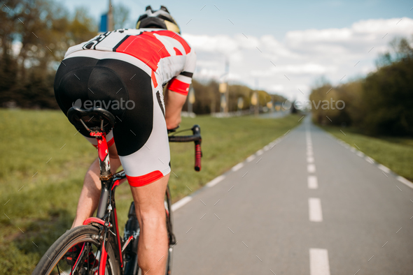 Cyclist on bike path, view from the rear wheel - Stock Photo - Images