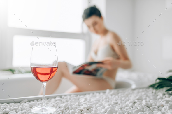 Glass of red wine, woman in bath on background - Stock Photo - Images