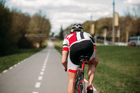 Cyclist rides on bicycle, side view - Stock Photo - Images