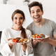 Portrait of a happy young couple holding dinner plates - PhotoDune Item for Sale