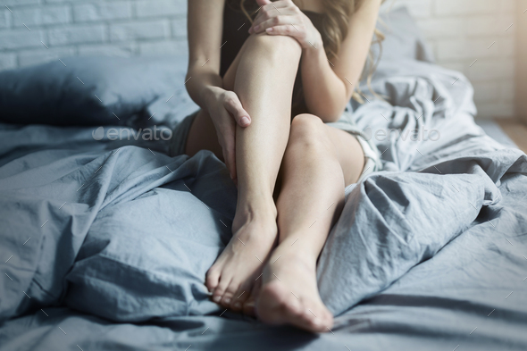 Female tired legs in bed at home - Stock Photo - Images