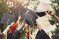 A group of graduates throwing graduation caps in the air - PhotoDune Item for Sale