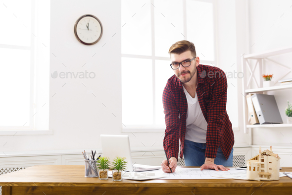 Young architect working with blueprints in the office - Stock Photo - Images