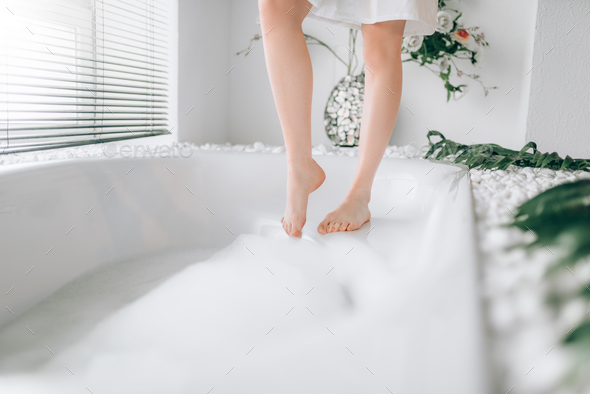 Female person legs dips into the bath with foam - Stock Photo - Images