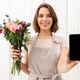 Happy florist woman standing with flowers showing display of mobile phone. - PhotoDune Item for Sale