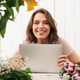 Cheerful florist lady standing with flowers using laptop computer. - PhotoDune Item for Sale