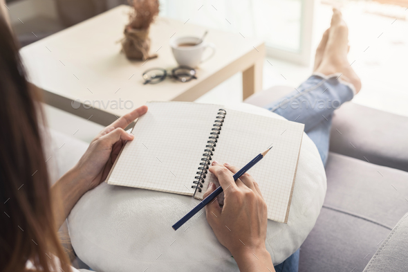 Young woman writing diary at cozy home on sofa in living