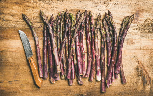 Fresh purple asparagus over wooden background - Stock Photo - Images