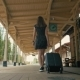BackView of Woman in Black Dress Walking with Suitcase Along Train Station - VideoHive Item for Sale