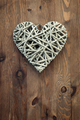 Reed heart hanging against a rustic wooden background. - PhotoDune Item for Sale