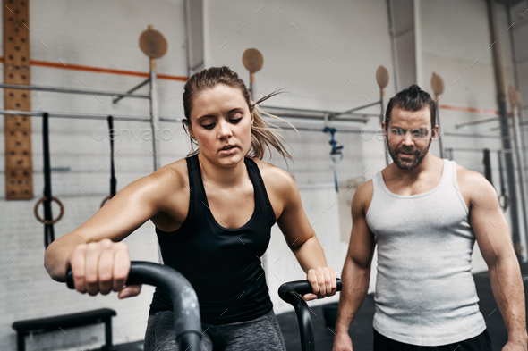 Fit young man watching his gym partner ride a bike - Stock Photo - Images