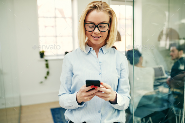 Smiling businesswoman standing in an office sending a text message - Stock Photo - Images