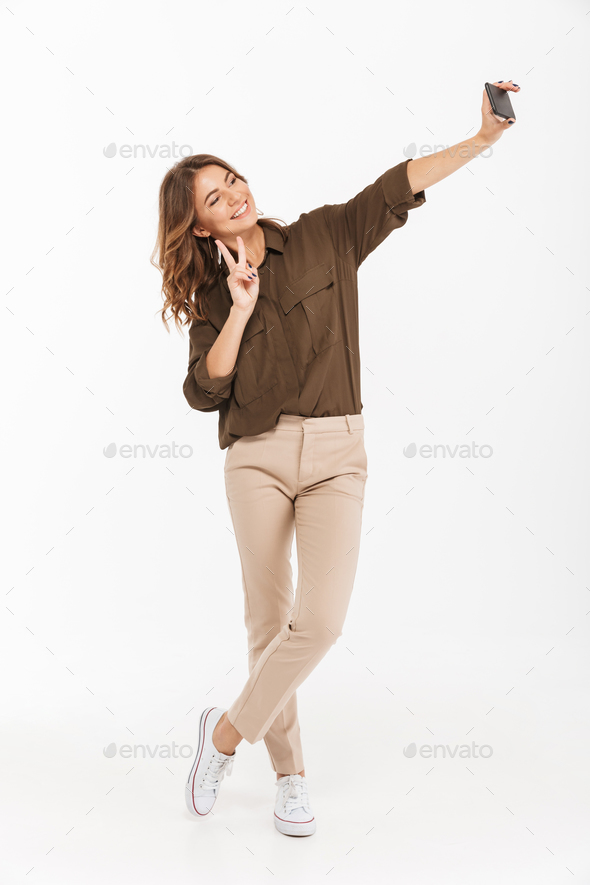 Full length portrait of a smiling young woman - Stock Photo - Images