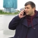 A Man Is Talking on a Mobile Phone Against the Backdrop of a Cityscape. - VideoHive Item for Sale