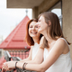 Two female friends talking and laughing at the balcony - PhotoDune Item for Sale