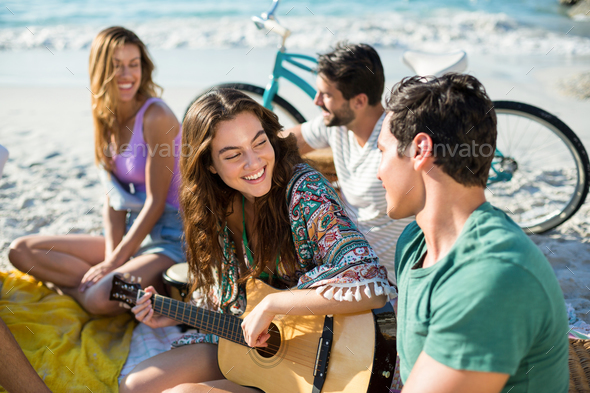 Happy friends enjoying while sitting at beach - Stock Photo - Images