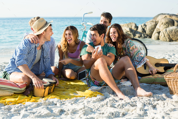 Friends laughing while sitting on shore - Stock Photo - Images