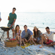 Smiling friends having drinks by barbecue at beach - PhotoDune Item for Sale