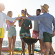 Friends toasting while standing by barbecue at beach - PhotoDune Item for Sale