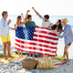 Friends holding American flag on shore at beach - PhotoDune Item for Sale