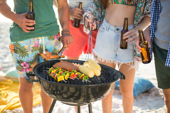 Friends having drinks by barbecue on shore - Stock Photo - Images