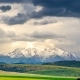Snow-capped Mountain Top Against a Backdrop of Thunderclouds and Wheat Fields in Summer - VideoHive Item for Sale