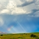 The Rainbow Glows in the Sunlight Against the Background of Dark Clouds - VideoHive Item for Sale