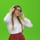 Girl in Glasses Listens To Music on Headphones . Green Screen - VideoHive Item for Sale
