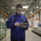 A Man Is Working in a Factory with a Digital Tablet, He Is Dressed in a Blue Uniform. Factory Worker - VideoHive Item for Sale