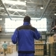 Engineer in in Blue Uniform Is Walking Through Factory and Talking on the Mobile Phone - VideoHive Item for Sale