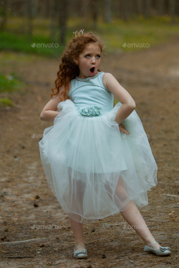 Little emotional girl walks in a summer forest in a dress - Stock Photo - Images