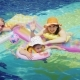 Happy Parents with Children Are Swimming in the Pool. Hold on To an Air Mattress, Look at the Camera - VideoHive Item for Sale