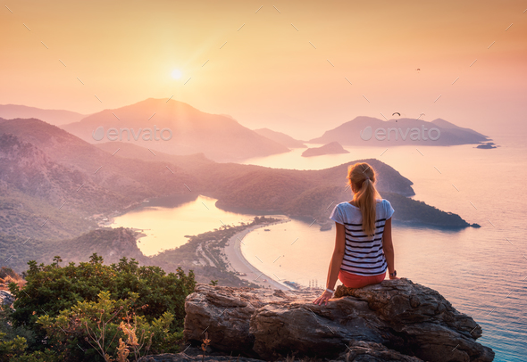 Young woman sitting on the top of rock and looking at the seasho - Stock Photo - Images