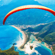 Paraglider tandem flying over sea with blue water and mountains - PhotoDune Item for Sale