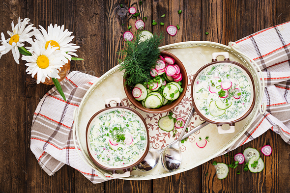 Cold soup with fresh cucumbers, radishes with yoghurt in bowl on wooden background.  - Stock Photo - Images