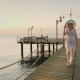 A Woman in a Pair and Hat Walks on the Pier in the Early Morning. Breathes in the Fresh Air. - VideoHive Item for Sale