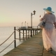 A Woman in a Pair and Hat Walks on the Pier in the Early Morning - VideoHive Item for Sale