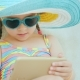 A Little Girl in a Swimsuit Resting on a Lounger, Using a Smartphone. Holiday with Children - VideoHive Item for Sale