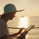 A Woman Uses a Tablet on Vacation. Sits Against the Background of the Rising Sun Above the Sea - VideoHive Item for Sale