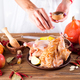 Chicken in a plate with spices apple and orange on a wooden table. The woman hands sprinkle  - PhotoDune Item for Sale