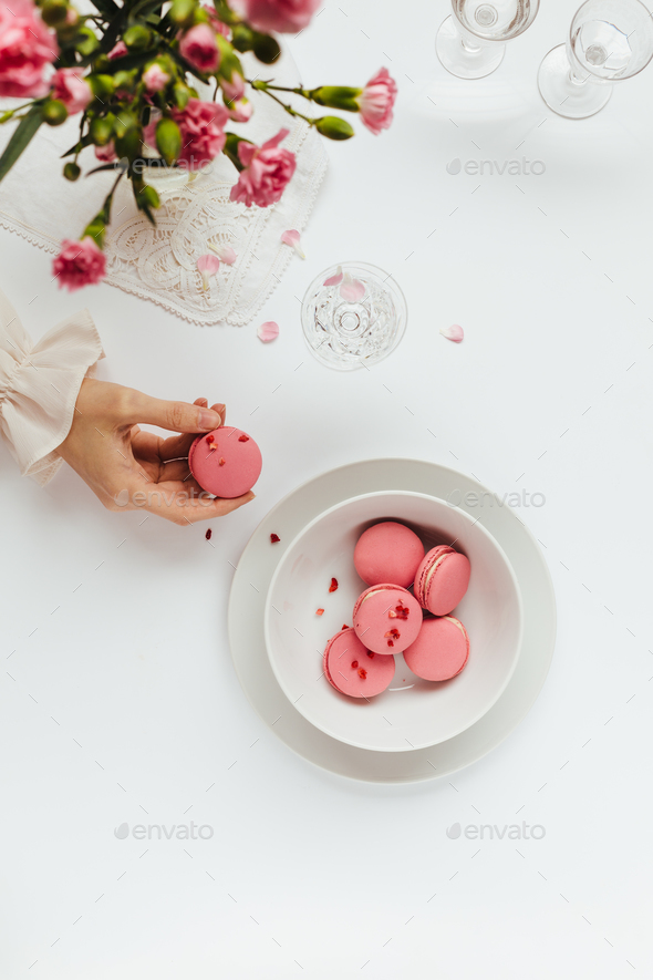 Woman's Hand Taking Strawberry Macaron from White Bowl - Stock Photo - Images