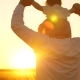 Dad Bears Baby Sitting on His Shoulders at Sunset of Golden Sun - VideoHive Item for Sale