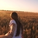 Laughing Girl Runs Across the Field with Wheat Holding a Man's Hand in the Glare of the Golden Sun - VideoHive Item for Sale
